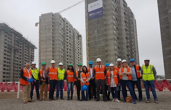 Mission delegates stand in front of apartment blocks in the athletes village