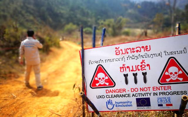 Démineur de Handicap International au Laos à côté d'un panneau indiquant le danger des restes explosifs de guerre.